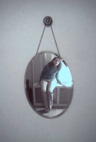 Wall mirror with teenager reflected in it